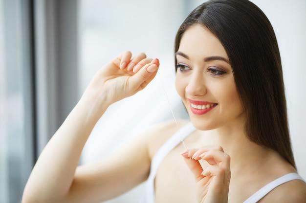 Здоровье зубов. женщина с красивой улыбкой зубной нитью здоровые зубы.