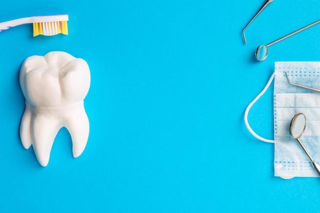 치과 위생 및 건강 개념입니다. 치과 도구 또는 도구 치과 탐험가, 하얀 치아 모델 근처의 절차 얼굴 마스크에 있는 치과 거울, 밝은 파란색 배경에 칫솔. 자유 공간.