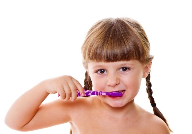 Гигиена полости рта. счастливая маленькая девочка чистит зубы