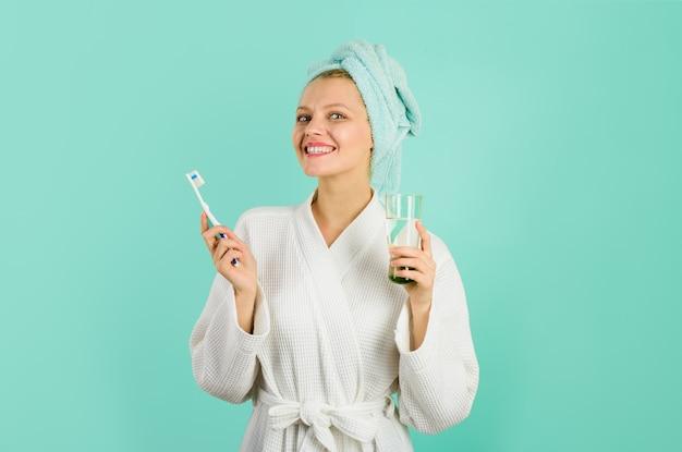 Гигиена зубов улыбающаяся женщина с зубной щеткой и стаканом воды, утренние процедуры зубной пасты