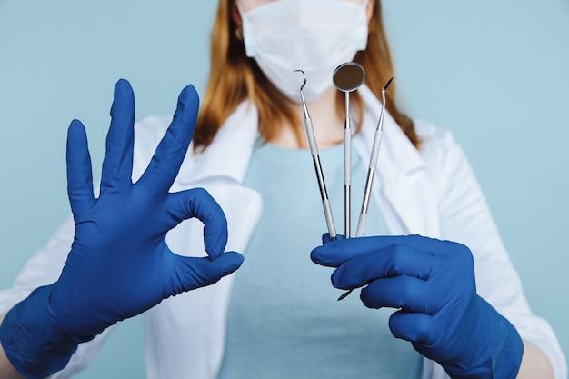 Стоматолог-гигиенист с модельными зубными протезами и стоматологическими инструментами на синем