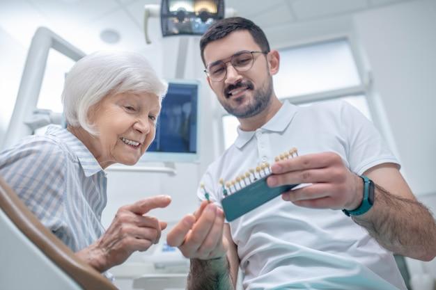 Зубные имплантаты. молодой стоматолог мужского пола, выбирая зубной имплант со своим пациентом