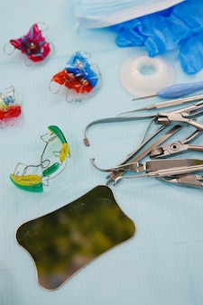 医療用テーブルの歯科用器具と入れ歯。青い背景の歯の治療とモデルのための実験器具。義肢装具士のオフィス。衛生士への検査の概念。コピースペース
