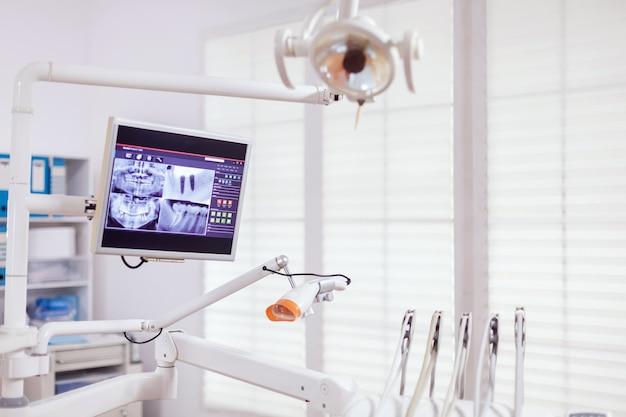 Стоматологические инструменты и инструменты в кабинете стоматолога. кабинет стоматологии, в котором никого нет, и оранжевое оборудование для лечения полости рта.