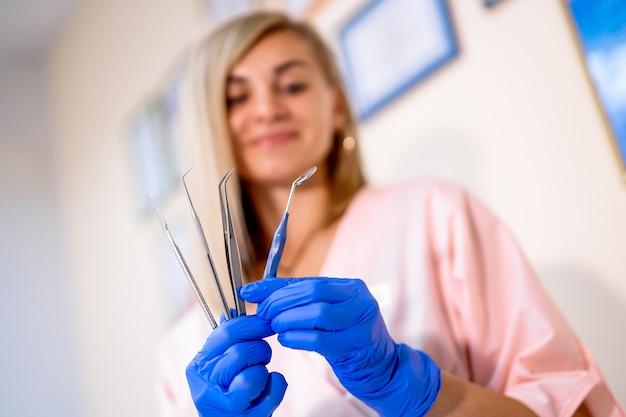 歯科用器具。手に歯科用ツール。働く専門の女性歯科医の医者