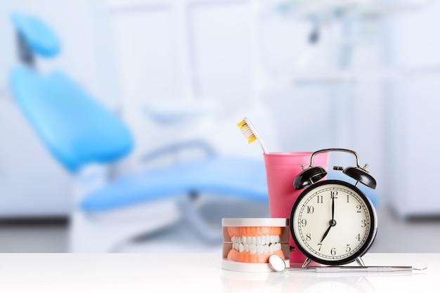 人間の顎の近くの歯科用器具、目覚まし時計、歯ブラシ