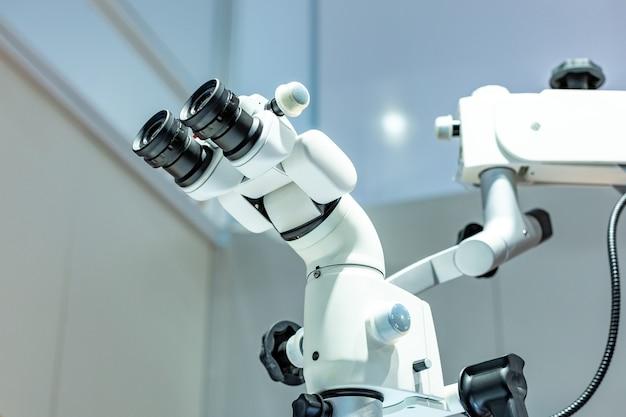 Стоматологический микроскоп на фоне современной стоматологии. медицинское оборудование. стоматологический операционный микроскоп с поворотным двойным биноклем.