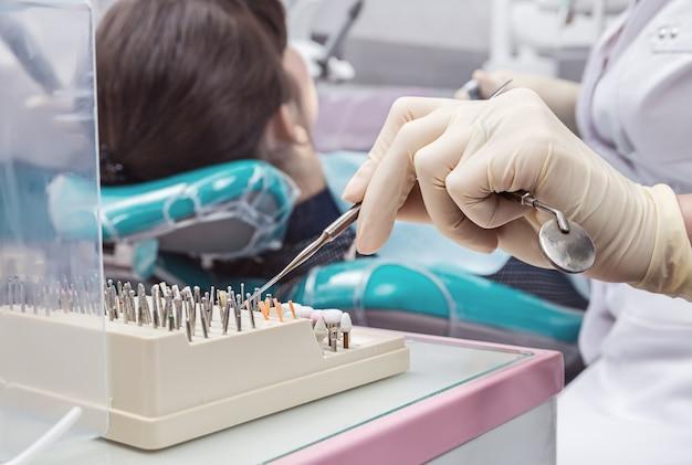 Стоматологический кабинет. рука доктора в перчатке с инструментами.