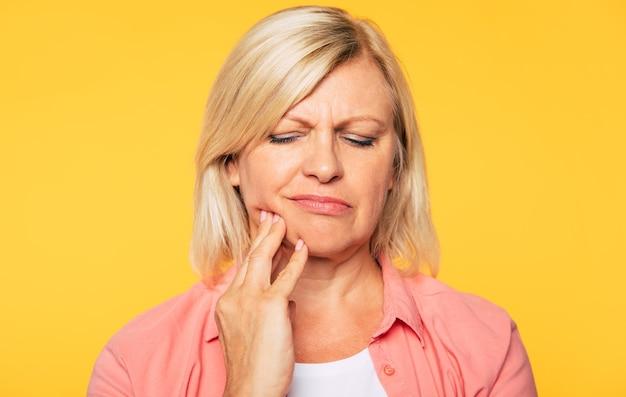歯の痛み。強い歯痛を持つ年配の女性のクローズアップの肖像画は彼女の頬に触れています
