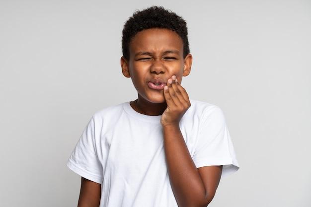 Зубная боль у детей. портрет нездорового маленького мальчика, касающегося щеки, чувствуя сильную зубную боль, проблемы со здоровьем полости рта. крытый студийный выстрел, изолированные на белом фоне