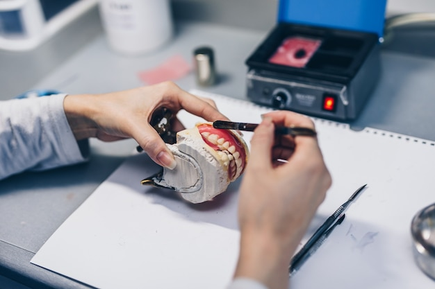 Dental prosthesis, female hands working on the denture. selective focus.