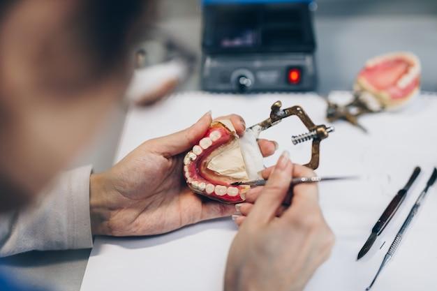 歯科補綴物、補綴物は機能します。義歯の作業中の義肢装具士の手のクローズアップ。セレクティブフォーカス。
