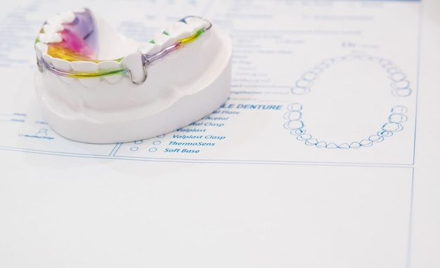 Dental retainer orthodontic appliance on the colour background.