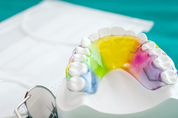 Dental retainer orthodontic appliance and dental tools on the colour background.