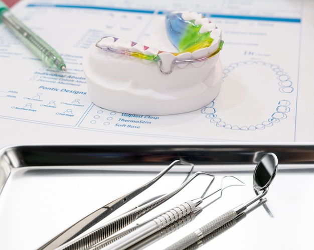 Dental retainer orthodontic appliance and tools on the colour background.