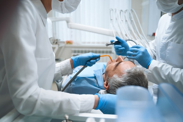 Dental specialist and nurse are helping man with teeth problems and giving him filling in clinic