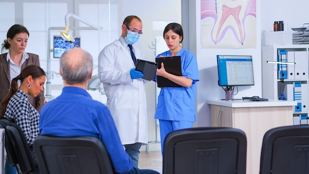 歯科医が患者診察前に口腔病クリニックの待合室に立っている助手と話し、医師がタブレットを見ながらクリップボードにメモを取ります。