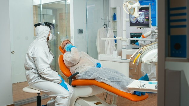 Dental specialist with coverall talking with senior patient before examination during pandemic covid-19. concept of new normal dentist visit in coronavirus outbreak wearing protective suit and face sh