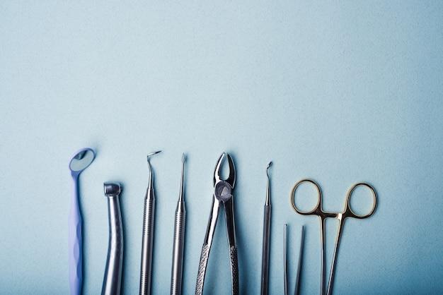 복사 공간이 있는 밝은 파란색 배경의 치과용 강철 도구