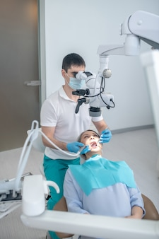 Dental surgery. male dental surgeon working with patient and using optical medical instrument