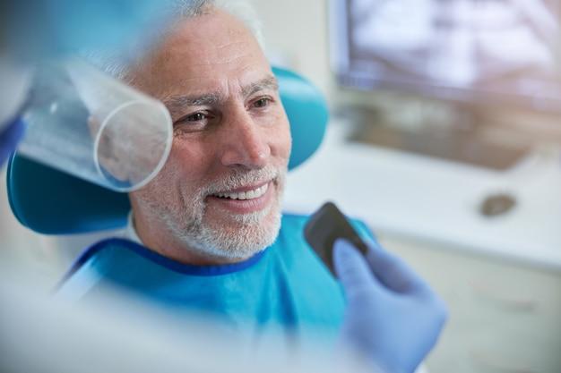 Зубной техник держит небольшую карточку с пленкой, готовя пациента к стоматологическому рентгену