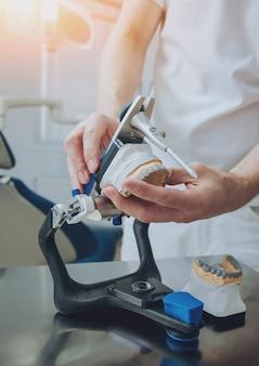 Зубной техник работает с артикулятором в стоматологической лаборатории