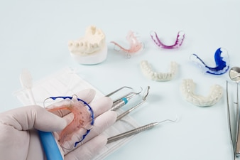 Dental  tools  and retainer orthodontic appliance on the blue background.