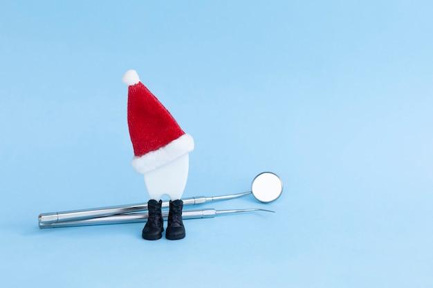 サンタの帽子の歯科用ツール新年のクリスマスの歯。ミラー、治療予防口を調べるためのプローブ