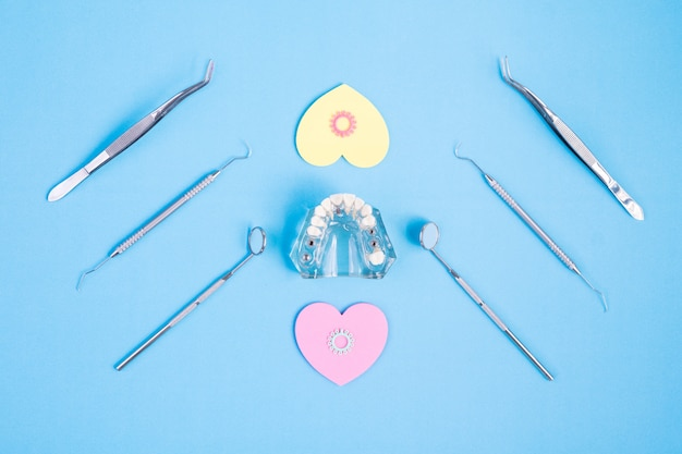 Dental tools use for dentist on the blue background, flat lay, top view.