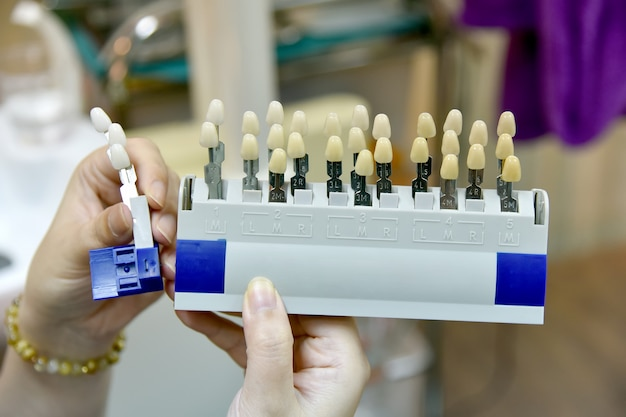 Dental tooth shade guide, dentist matching color tone of dental chart for teeth whitening treatment at clinic.