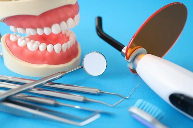 Стоматологическая уф-лампа для пломбирования зубной челюсти и инструменты на столе концепция стоматологических услуг