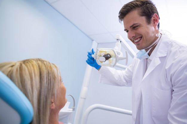 Dentist adjusting lamp while looking at patient in medical clinic
