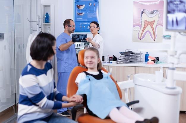 診断について話し合う小さな女の子の顎のレントゲン写真を持っている歯科医院の歯科医と助手..歯の間に彼女の母親と一緒の子供は椅子に座っているstomatologでチェックします。