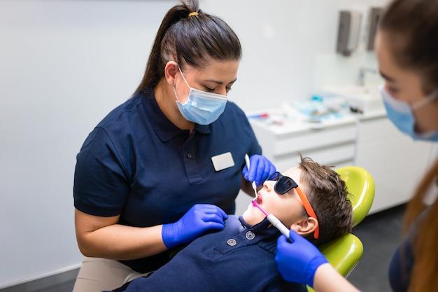 歯科医と助手がティーンエイジャーのための予防的な歯垢洗浄を行います