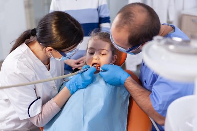 大きな服を着て椅子に座っている少女のための歯科治療中に器具を使用する歯科医と助手。歯の口腔病学クリニックにいる子供を持つ母親は、最新の器具を使用して検査します。