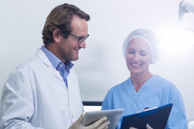 Стоматолог и ассистент стоматолога, работающий над цифровым планшетом