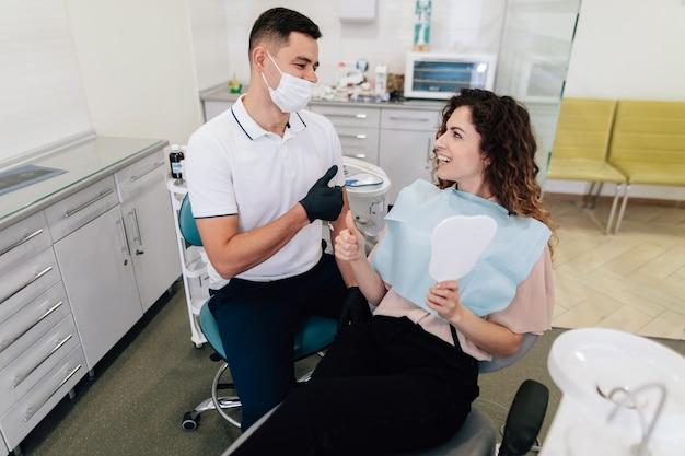 Стоматолог и пациент счастливы и улыбаются