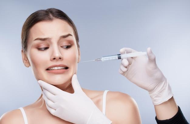 歯科医と患者、ヘルスケア、歯科医のための口腔病学の概念。歯科医の手で注射器を見ている白い歯を持つ非常に怖い女の子
