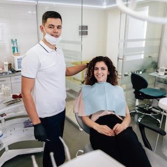 Стоматолог и пациент позирует и улыбается