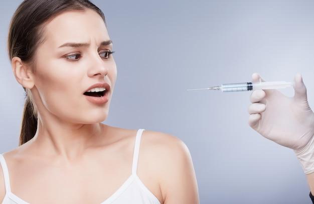 歯科医と患者、歯のケア。ヘルスケア、歯科医のための口腔病学の概念。注射器を見て真っ白な歯を持つ怖い女の子