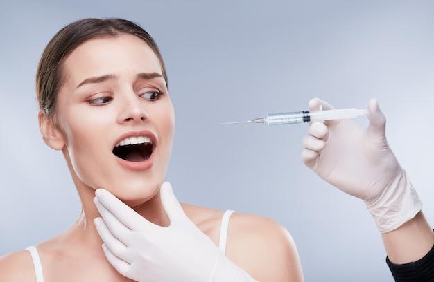 歯科医と患者、歯のケア。ヘルスケア、歯科医のための口腔病学の概念。歯科医の手で注射器を見ている真っ白な歯を持つ非常に怖い女の子