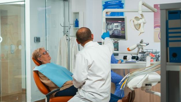 患者の診察中に歯科x線撮影を求める歯科医。歯科矯正医と看護師が現代の歯科医院で一緒に働いており、歯科矯正医が年配の女性に歯のレントゲン写真を説明しています