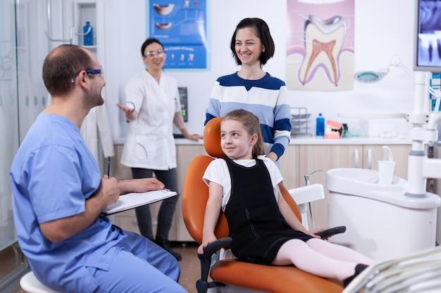 Помощник стоматолога дает хорошие новости родителям ребенка после осмотра зубов в стоматологическом кабинете. ребенок с матерью во время осмотра зубов у стоматолога, сидящего на стуле.