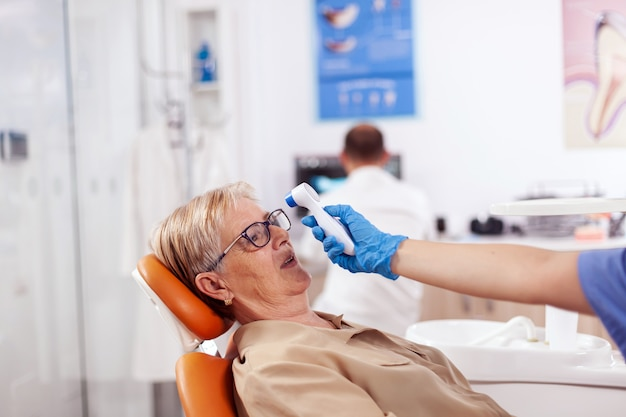 Dentist assistant holding digital body temperature indicator in front of patient forhead sitting on chair. medical specialist in dental clinic taking patient temperature using digital device.