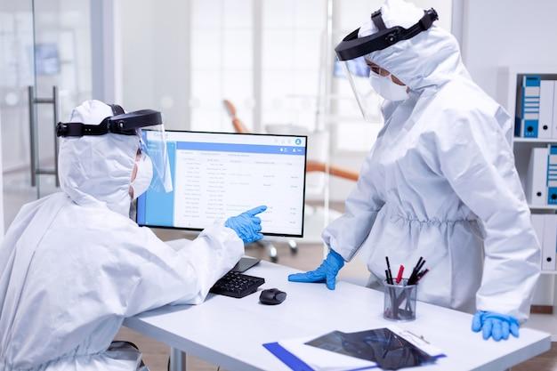 患者の順番待ちリストを指しているppeスーツの歯科助手。安全対策として、歯科受付でコロナウイルスのパンデミックに対する保護具を着用している医療チーム。