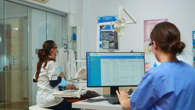 歯科助手がコンピューターで予約を取り、歯科医が歯科インプラントを示すデジタル画面を指しています。モニターの口腔病学クリニックで歯のx線写真を説明する口腔病専門医。