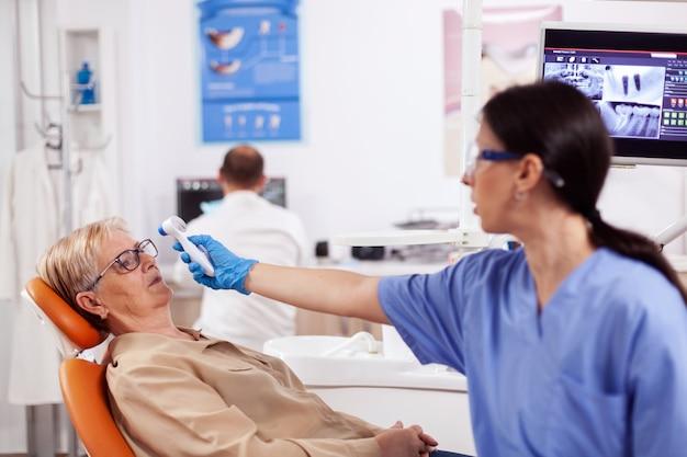 相談中に体温計を使って年配の女性の体温を測定する歯科助手。デジタルデバイスを使用して患者の体温を測定する歯科医院の専門医。