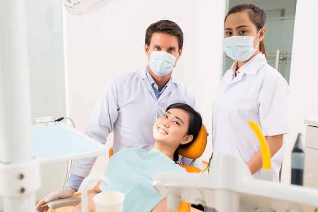 Dentist, assistant and smiling patient