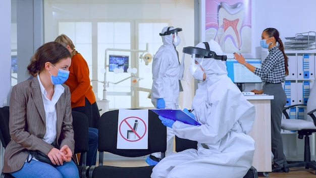 Dentist assistant with ppe equipment talking with patient before consultation during coronavirus epidemic sitting on chairs in waiting area keeping distance. concept of new normal dentist visit.
