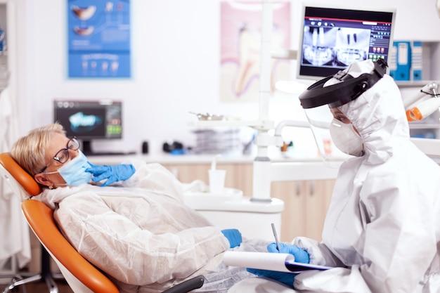 コロナウイルスに対する保護具を着用している患者に質問する歯科医の助手。歯科医院での診察中に防護服を着た年配の女性。